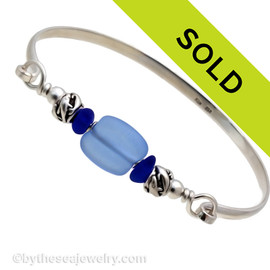Two pieces of beach found sea glass in bright cobalt blue on this solid sterling silver sea glass bangle bracelet. The center bead is handmade by a glass artist and resembles bright medium blue sea glass. Finished with sea life beads that have images of dolphins frolicking around. SORRY THIS SEA GLASS JEWELRY ITEM HAS BEEN SOLD!