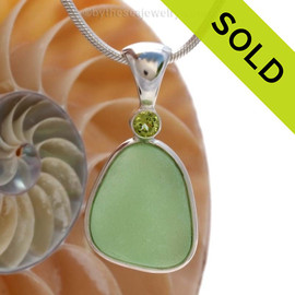 This beautiful Bright Sea Green sea glass  piece is set in our Deluxe Wire Bezel© pendant setting with a genuine Peridot gem. Sorry this piece of Sea Glass jewelry has been SOLD!
