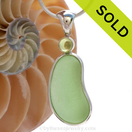 "This beautiful Bright Vivid Seafoam Green sea glass pendant is set in our Deluxe Wire Bezel© pendant setting with a genuine Peridot gem.  A genuine domed genuine peridot 6MM gem is set in a ""tube bezel"" setting. This is NOT a glued setting but painstakingly burnished to enclose the gem."