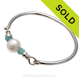 A stunning sea glass bracelet on our best sterling bangle. The aqua sea glass nestles a LARGE fresh water pearl. Sorry this Sea Glass Jewelry item has been sold!