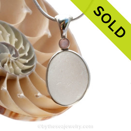 A very thick and piece of top quality pure white English sea glass pendant set with a pink mussel gem in a tube bezel setting. Sorry this piece of Sea Glass Jewelry has been sold!