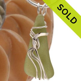 """A beautiful natural peridot or pale olive green sea glass pendant set in our original signature """"Waves"""" setting in solid sterling silver. Sorry, this Sea Glass Jewelry selection has been SOLD!"""