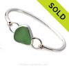A nice piece of yellowy seafoam green sea glass set in fine and sterling silver in a classic bangle bracelet. Sorry this piece of Sea Glass Jewelry has been sold!