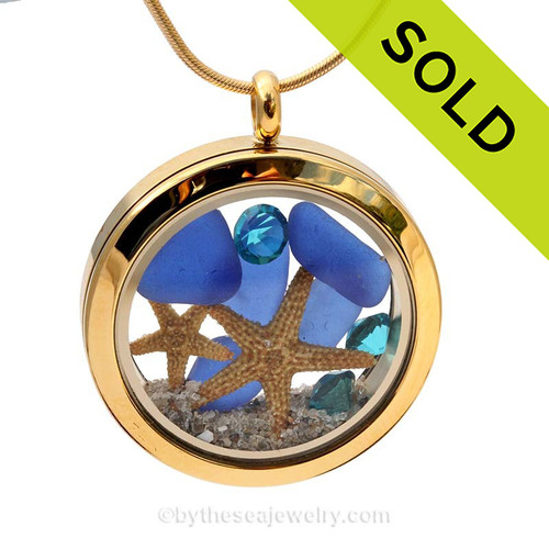A gold tone stainless steel locket necklace with real blue beach found sea glass pieces and two real starfish and finished with Turquoise crystal gems.