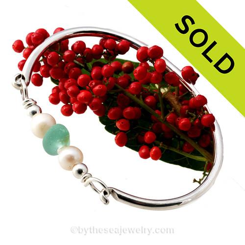 A stunning aqua green natural sea glass bangle bracelet with fresh water pearls.