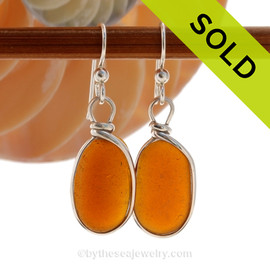 Beautiful vivid amber brown sea glass pieces left just the way they were found on the beach in Puerto Rico are set in our Original Wire Bezel© setting in Solid Sterling Silver SOLD - Sorry these Sea Glass Earrings are NO LONGER AVAILABLE!
