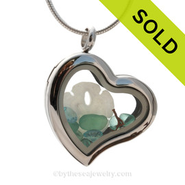 Our new heart lockets make this aqua sea glass really shine! Free Floating and changing like the tide, this piece includes genuine aqua sea glass, a baby sandollar, and aquamarine gems which are perfect for any May Sea Glass Lover!