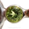 "A genuine brilliant cut peridot 6MM gem is set in a ""tube bezel"" setting."