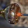 Pictured Here - Modern Art Glass on a Punty or Pontil. In a fisheye or pontil piece, you can see how the glass was pulled before being snapped off for final finishing. The Center of the glass remained hot and therefore stretched more as the outside cooled and was more stable. Most fisheye or pontil pieces from Seaham have this characteristic though many are just a hint of color on a tip of white.