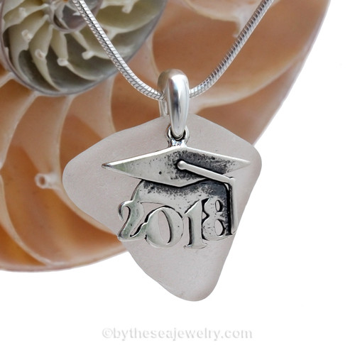 """A nice piece of white genuine sea glass with a solid sterling bail and detailed """"2018"""" graduation charm. This piece comes complete with our sterling 1MM snake chain."""