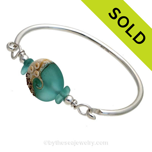VIVID Aqua Genuine Sea Glass Bangle Bracelet set with a handmade lampwork glass wave bead set with sterling details on a solid sterling round bangle bracelet. SOLD - Sorry this Sea Glass Bangle Bracelet is NO LONGER AVAILABLE!