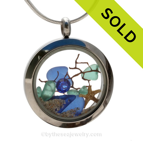 Beautiful aqua and blue sea glass combined in a stainless steel locket necklace with a real starfish, a bit of vintage seafan and a sapphire crystal gem. Finished with real beach sand.  SOLD - Sorry this Sea Glass Locket is NO LONGER AVAILABLE!