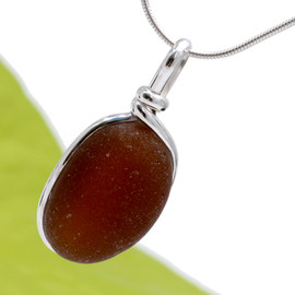 A rich dark rootbeer brown sea glass piece set in our Original Wire Bezel© setting. This sea glass is left just the way it was found in the beach, securely set in our signature sterling setting.
