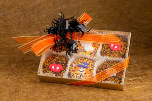 Chocolate enrobed Oreos with Halloween themed labels on orange & black foils OR  Halloween themed sugar art embellishments.
