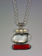 "This dramatic pendant features a slice of deep red coral, a freeform slice of natural mother-of-pearl and three white pearls all bezel set in sterling silver suspended from a  26"" silver ultraplate chain. No two pendants exactly alike. Pendant 2-1/2"""