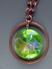 "Make a dramatic statement with this dichroic* Venetian glass disc pendant with sparks of verdant green, aqua and gold) suspended from a copper ultraplate hoop (2"") and looped chain 30""  Each specimen different and equally fascinating."