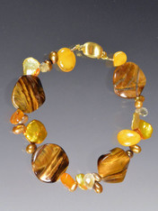 This bracelet features fluted tiger eye discs, yellow amber, gold pearls  - a perfect transition to fall. 7-1/2""
