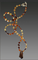 "This spectacular faceted hessionite garnet rope in tones of wine, sienna, and pale citrine spaced with faceted garnet and finished off with a huge smokey topax swirl pendant will be the most versatile item in your wardrope.  Wear it alone, pair it with shorter pieces or ropes.  28"" Topaz Swirl 1.5"""