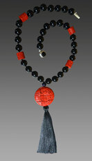 "I discovered this stunning deeply hand-carved cinnabar focal bead many years ago in San Francisco.  It forms the basis of this rare and dramatic necklace that features black Venetian glass and barrel shaped complementary carved red cinnabar beads finished off with a luxurious black silk tassel. Totally elegant and very limited.  22"" Tassel 6.5"""
