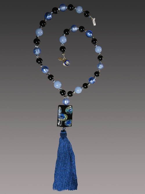 """This stunning on trend necklace features a """"Van Gogh"""" limited edition blue Starry Night Venetian glass rectangle with silk-knotted indigo,pale blue, and biack Venetian glass beads, a luxurious blue silk tassel, and a gold druzy sterling clasp.   Necklace 30"""" Silk Tassel 4-1/2""""  ONLY THREE AVAILABLE      *This authentic lampwork Murano Glass Bead is one of a kind, big and bold made with amazing skill and time. Named """"VanGogh"""" because the little paintings inside look like scenes from the paintings, they measure almost 2 inches in length, and the pattern is always different owing to the handwork. This particular bead features shades of black, luminous starry blue, and aqua."""