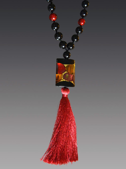 """This statement on trend necklace is all you need to make any outfit stand out. The starting inspiration is an amazing limited edition Venetian arlecchino (or harlequin) rectangle in luscious dots of wine rubino and 24K Gold Foil paired with an red silk tassel and hand-knotted Venetian. Necklace 24"""" Silk Tassel 6.5""""""""  There is only one artist in Venice who makes Arlecchino"""" beads and he has retired so there will not be any more of these coming."""