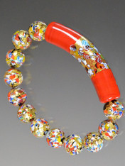 "Make a dramatic statement with one fabulous bracelet or stack it with others in complementary colors. This Klimt stretch bracelet features a limited edition 60 mm curved tube (named after the mosaic style renowned painter) with an exterior band of gold with small bits of mosaic (millefiori) embedded on a base of red Murano Glass.   Perfect for the holidays and everyday!  7-1/2-8""  VERY LIMITED"