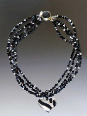"""Two opulent looks in one! Luxuriate in four strands of Grade AAA onyx dice specially ordered for this design randomly spaced with sterling Swarovski crystals. A dramatic Venetian glass freeform sterling black and silver tiger pattern heart suspended from a circle of onyx beads can be removed for an elegant torsade only look. ONLY TWO 18"""" (Longer lengths available on request)"""