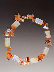 "This delightful collar will lift your spirits and make you glow in the sunny weather.  It features unusually multi-toned carnelian rectangles spaced with precious clusters of glass carved leaves, tourmaline and fire agate, finished off with a complimentary Swarovski Crystal sterling clasp.  18""."