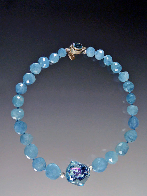 """If you love aquamarine and want to make a statement, this is for you. Grade AAA rich blue grduated aquamarine faceted beads frame a beautiful Venetian Sasso window center with flashes of aqua, pink and black. A custom blue topaz clasp completes the picture. 18"""""""
