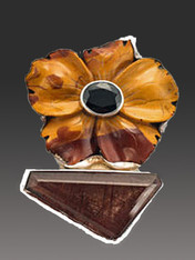 "This magnificent Amy Kahn Russell pin/pendant is just gorgeous and beautifully crafted like her early works. It features a large hand-carved jasper flower with tones of wine, bronze, and brown in an intricate pattern with a large garnet cabochon set in sterling silver in the center.  The flower perches on a rutilated quartz asymmetrical stone all bezel set in thick sterling silver. 2-1/5"" x 2"""