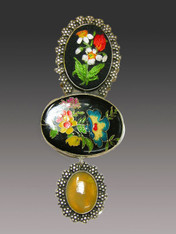 "This charming Amy Kahn Russell pin/pendant evokes bygone eras.  It features a brilliantly hand embroidered floral oval top, a large colorful enameled oval center and a yellow opal dangle all set in an intricately patterned sterling frame with a brass backing  Perfect for right now and all year. 4-1/2"" x 2"""
