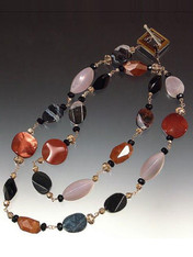 """A striking collage of shapes and colors! Faceted multi-agate slices artfully mixed with grey and black onyx, cognac Swarovski crystals, hand-wire linked and finished with a 14K square crystal toggle. Wear alone or pair with others. 42"""""""