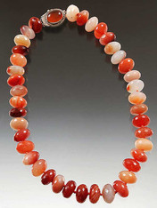 "Brighten your day with a sparkling 18"" collar of faceted grade AA carnelian flashing every tone from amber to deep orange. Japanese double hand-knotted with  red silk. A highlight 1""  carnelian sterling clasp can be worn side, center or back."
