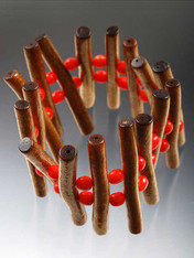 "Bronze stick coral and alternating red round coral form an impressive yin-yang bracelet that stretches to 8"" - 2"" high"
