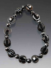 A charming stretch bracelet of intricately fitted hematite pieces add dimension and interest to this wearable piece.