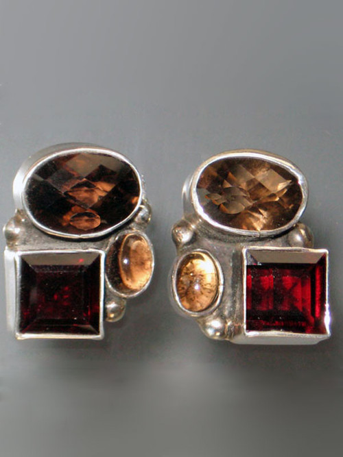 "These striking Amy Kahn Russell one-of-a-kind earrings feature one faceted and one smooth smoky topaz cabochons and a rich faceted garnet stone all bezel set in sterling silver. 1"" x 1"" Posts; can be converted to clips for an additional $12."