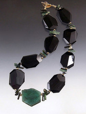 Remember when Angelina Jolie wore $2.5 million Brazilian emerald earrings to the Oscars? She was ahead of the curve because emerald green is the new hot color and Brazilian emeralds are the best. Many years ago I found a strand of Grade AAA natural Brazilian emerald slices. They aren't  polished gems like Jolie's but the real deal in their natural state and much more affordable. One 14 gram emerald slice is the centerpiece of a magnificent collar featuring faceted black onyx, green tourmaline,14K beads and clasp.  Each emerald slice is different and totally gorgeous.