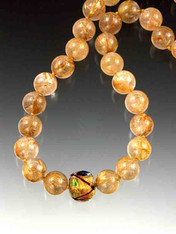 "A WEBSITE BEST BUY! this stunning strand of 16mm perfectly matched grade AA rutilated quartz orbs features one 24K gold foil ""Miro"" Venetian glass cube and a 14K ball clasp. 17""  NOTE: The 16mm strand in this picture has been sold but the identical collar is available with 14mm grade AA rutilated quartz- slightly smaller but the same superb quality."