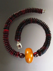 "This magnificent necklace features natural red-toned horn wheels, two large faceted transparent cherry amber beads from my personal collection, a spectacular 1"" x 1-1/2"" antique opaque butterscotch amber wheel.  25"""