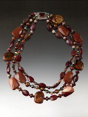 An absolute showstopper.  This torsade features a random mix of goldstone, Australian and other jaspers, with copper Swarovski crystals and a custom Pietersite sterling clasp custom made in Peru.  A beauty to wear in many ways. Longest strand 21""