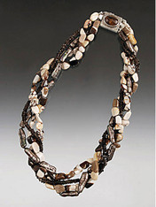 A torsade of freshwater pearls, smokey topaz, and extremely rare Australian Peanut wood*adds an exciting jungle accent to any ensemble. A custom South African Pietersite sterling silver clasp can be worn as a center or side accent. 19""