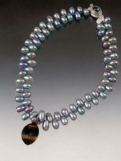 "A rare blue tiger eye swirl suspended on a strand of luminous large peacock blue ""firecracker"" pearls. 17-1/2"""