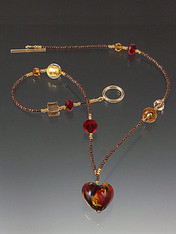 This one of a kind Venetian baby heart features 24K mingled with swirls of ruby, garnet and orange-gold on a bronze chain with tiny glass beads with Swarovski crystal stations.