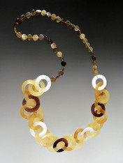 """This lightweight on trend necklace features luminous natural makabibi shell,horn, and mother-of-pearl linked circles in tones of amber, tortoise, dark brown and white with smaller natural horn discs around the neck for extra comfort.  22"""""""