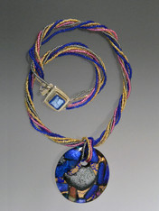 "A true Murano glass beauty custom ordered from Venice.  This design features a very limited edition 50mm curved round pendant of fused dichroic glass with flashes of plum, cobalt blue, sage green and light purple, suspended from a torsade of tiny seed beads in complementing colors and a dichroic glass sterling clasp.  The necklace is 19"" the pendant is 2""  ONLY TWO (no longer available)  Each pendant is different in its pattern but all are equally beautiful."