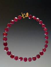 "I've been searching for years to find affordable fine quality rubies to replace the two that sold out.  It's almost impossible to find any up to my standard but recently I came upon two gorgeous strands of rich red faceted ruby coins which I designed in a simple classic collar with 18K beads and an 18K toggle clasp. If you are a ruby lover, get these while they're still available. 18"" ONLY TWO!"
