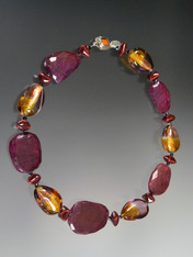 This spectacular one-of-a-kind necklace featuares the last of my raw ruby slices, limited edition Venetian tricolor amethyst, amber, 24K gold transparent Lido* pear shaped beads, Greek enameled grenadine stations, garnet Swarovski crystals and a vintage amber clasp. 20""