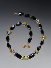 "This necklace  features a limited edition 60mm Venetian glass focal curved ""Klimt"" tube of black Murano Glass with a center exterior section of 24K gold with small bits of embedded millefiori mosaic resembling a Klimt painting. The rest of the necklace features onyx swirls, round Klimt mosaics, and 24K Swarvoski plated beads.  18"""