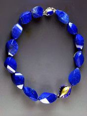 Fine lapis is becoming increasingly rare and expensive.  This one-of-a-kind statement necklace features grade AAA lapis faceted swirls with a 24K blue edged Venetian glass focal highlight and a lapis sterling clasp. 18""