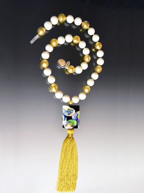 "This stunning on trend necklace features a limited edition ""Van Gogh"" Venetian glass rectangle with silk-knotted ivory and 24K gold foil venetian glass beads, a luxurious gold silk tassel, and a gold druzy sterling clasp.   Necklace 30"" Silk Tassel 4-1/2"""